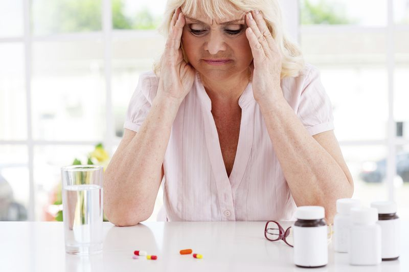 Feeling bad. Depressed senior woman holding head in hands and looking at the pills laying on the table