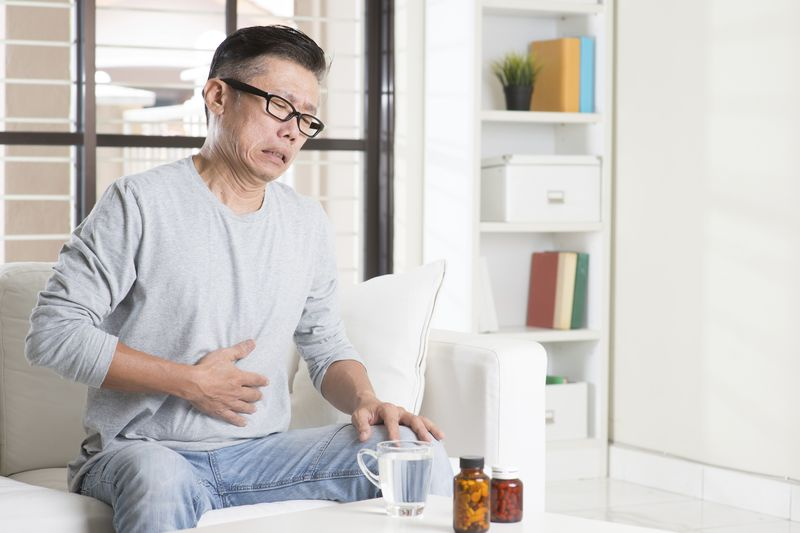 Mature 50s Asian man stomachache,  pressing on stomach with painful expression, sitting on sofa at home, medicines on table.